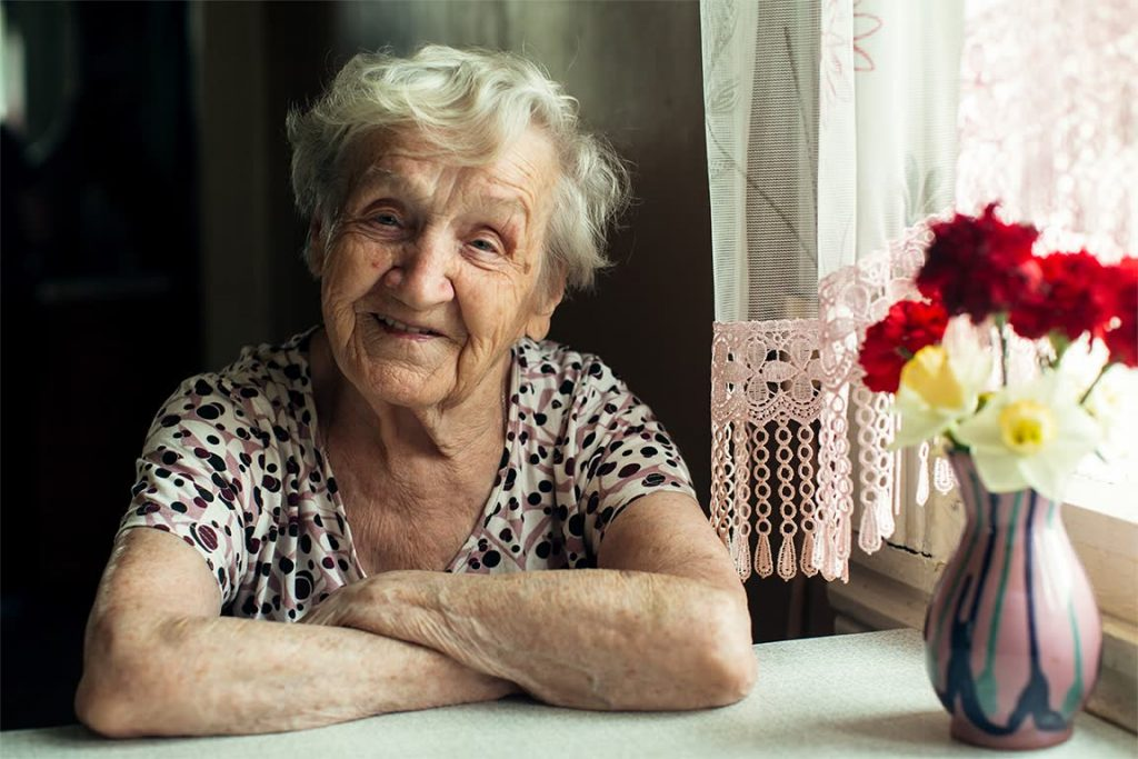 Elderly woman smiling next to a window.